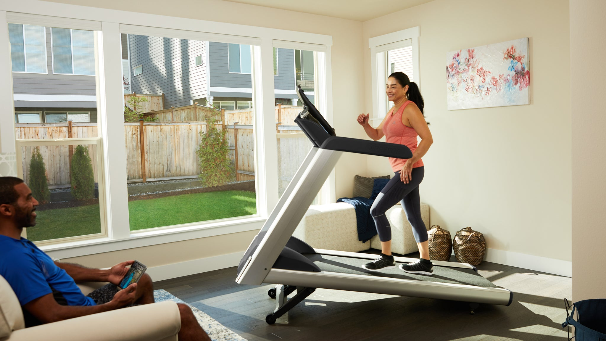 Woman works out on a walking treadmill as a man exercises in the room