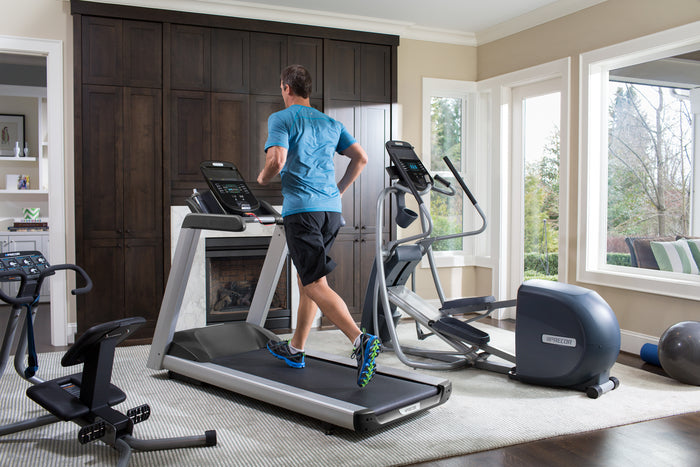 Man running on his Precor TRM 445 treadmill in his home gym that also includes EFX 447 elliptical fitness crosstrainer, and 240i StretchTrainer