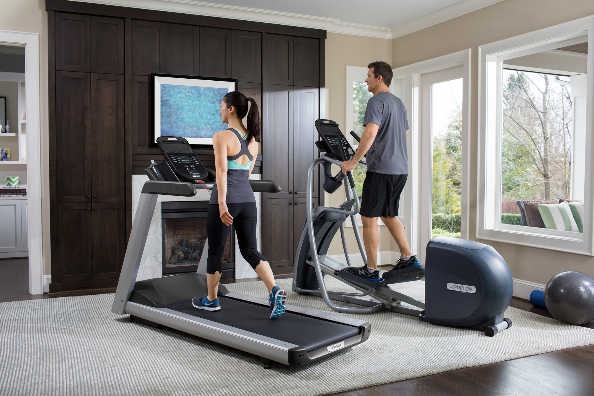 Woman walks on a treadmill, TRM 445, and man is on an elliptical, EFX 447, in their living room