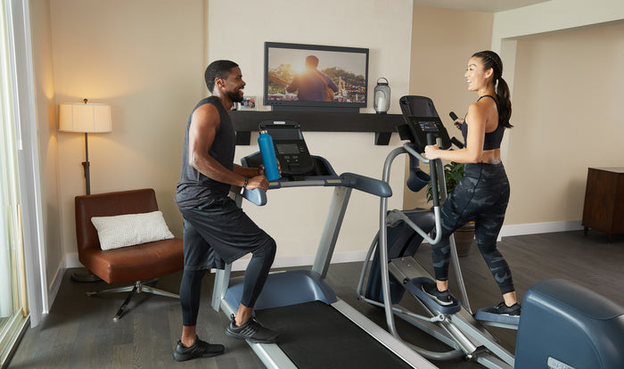 Woman working out on Precor EFX 447 elliptical next to a Precor TRM 445 treadmill with man leaning on arm of treadmill chatting after workout at home