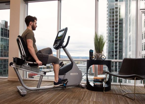 Man working out at home on a Precor RBK 885 recumbent stationary bike