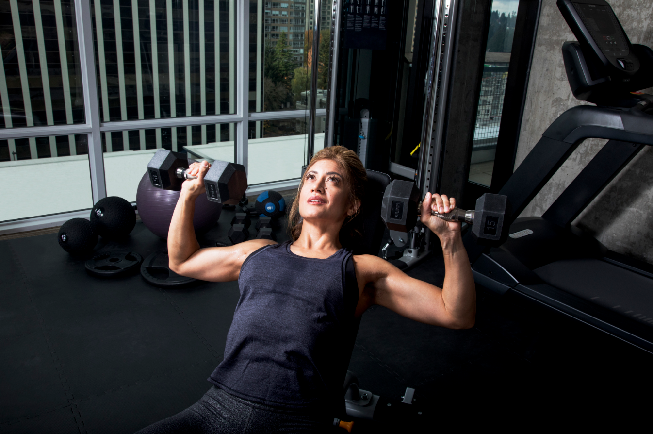 Female working out in her home gym using dumbbells on a Precor DBR 119 adjustable bench with a Precor TRM 731i Interval treadmill and Precor FTS Glide functional strength training system in the room
