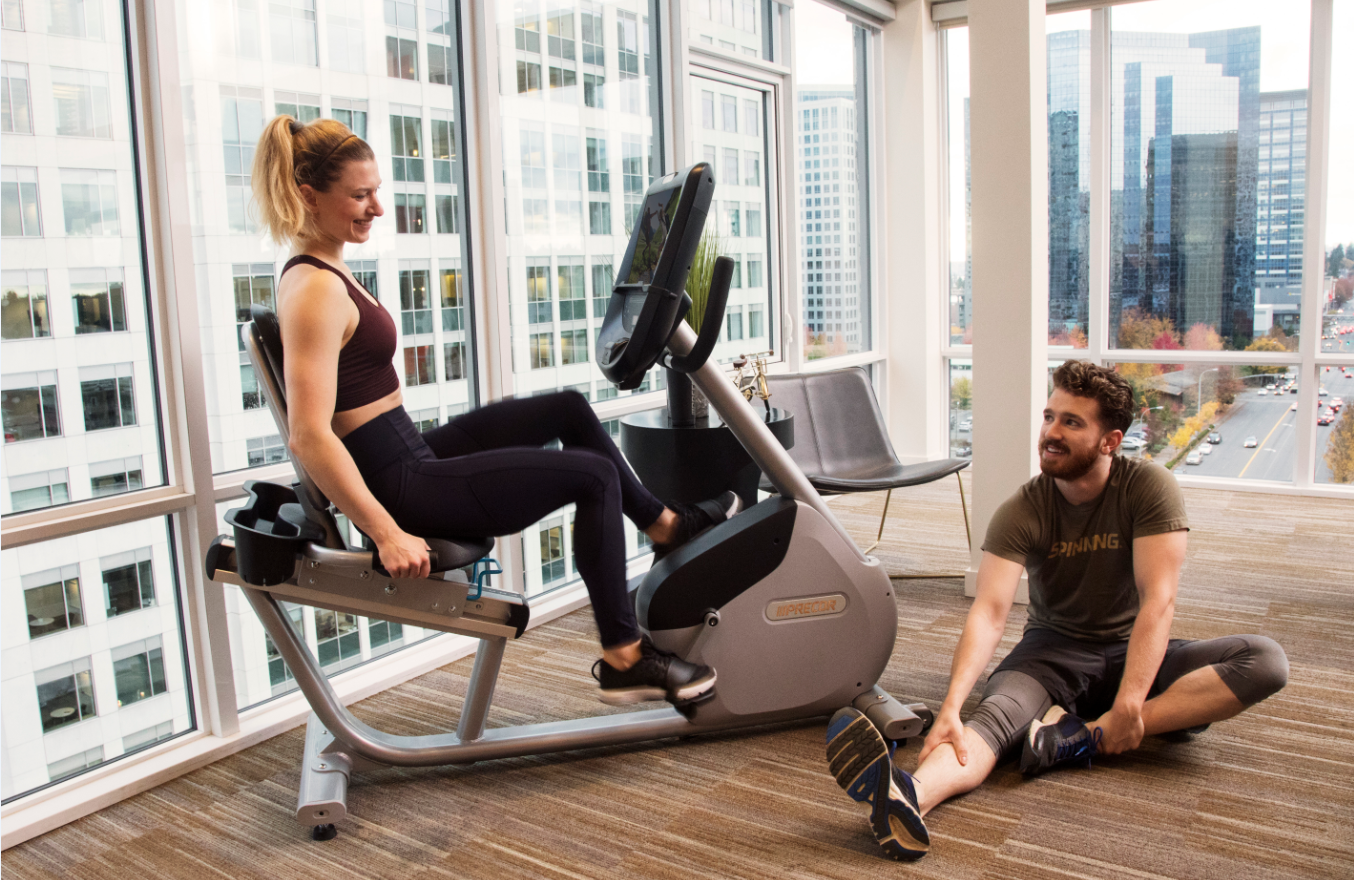 Female on a Precor RBK 865 recumbent bike with a man on the floor stretching