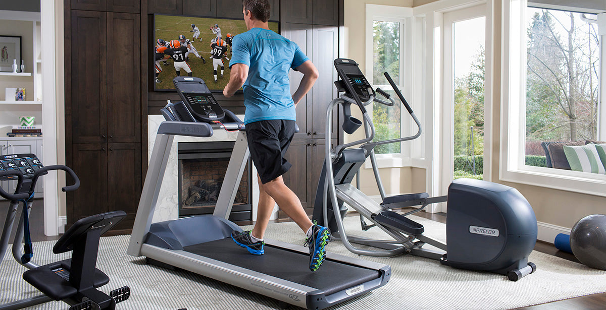 Person running in their home gym on a Precor treadmill, with an Precor elliptical and Precor StretchTrainer.
