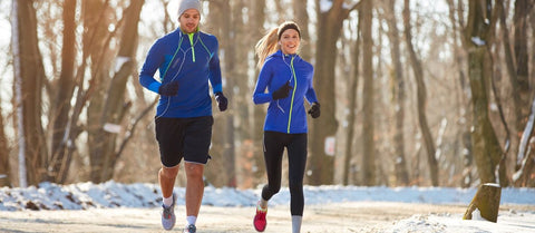 two people running outside during the winter, snow on ground