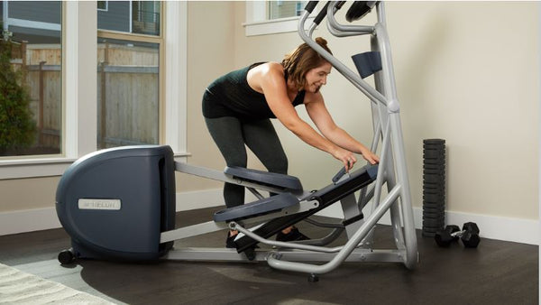 Woman manually adjusting the incline of her Precor home elliptical