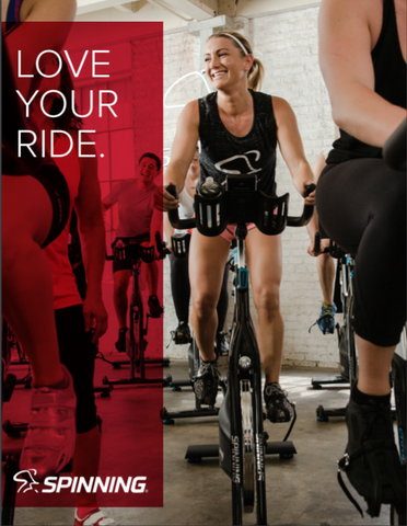Happy exercisers working out in a professional gym setting on Precor Spin bikes