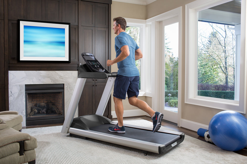 Man runs on Precor home treadmill, TRM 445, in the living room