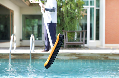 Brushing swimming pool sides and surface with pool brush