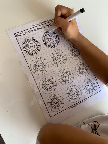 Child writing on laminated multiplication worksheet