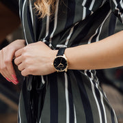Gold and black Stainless Steel Classic Watch with a black Full Grain Leather Strap for women by GenerationNow, Model Achilles, worn by model