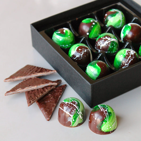Dark chocolate bonbons painted in green and filled with a peppermint filling and After Eight pieces.