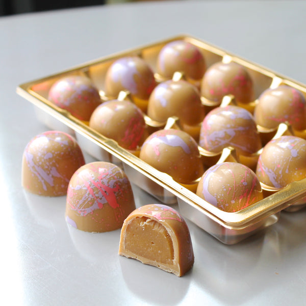 Blonde caramel chocolate bonbons with pink and purple
