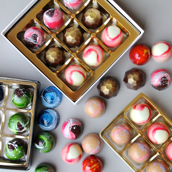 Colourful chocolate bonbons spread out on a table, seen from above