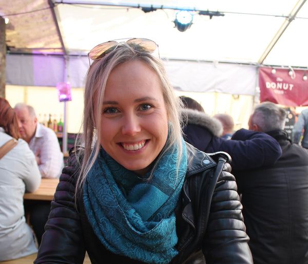 Blonde woman smiles to the camera while eating churros at a food market in York.