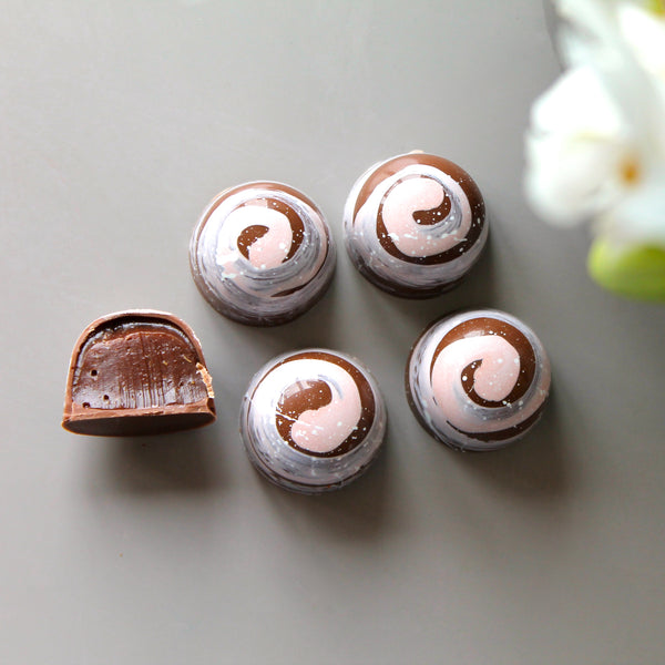 Milk chocolate bonbons with a pink swirl on top and flavoured with cinnamon and cardamom. Displayed next to an orchid.