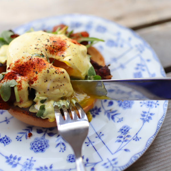 Daily Kneads Bagel Hollandaise with Eggs Benedict Recipe on Blue Plate with Coffee