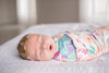 floral swaddle blanket in pinks and blue, lightweight and soft