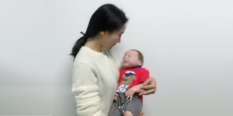 a woman holding a reborn baby doll