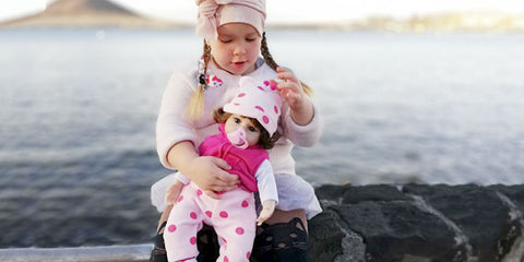 girl play with a lifelike baby doll