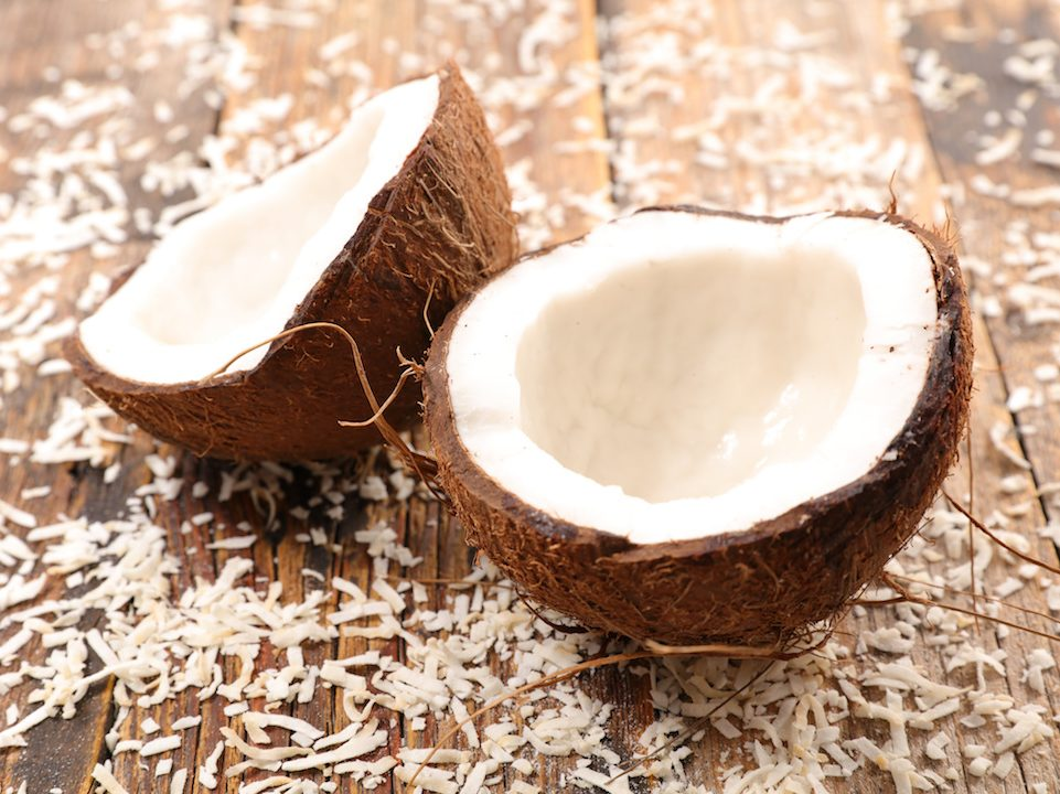 Broken coconut surrounded by coconut flakes on a wooden board