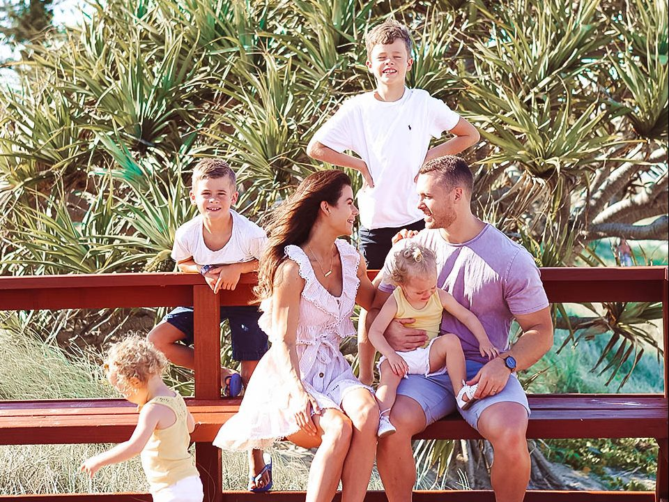 Sophie Guidolin and husband at the beach with kids|Evie and Aria with their brothers sitting on stairs||||