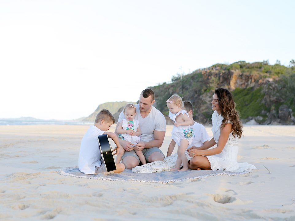 Four kids and parents at the beach wearing white|