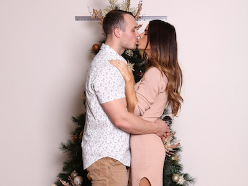 Sophie Guidolin and Nathan Wallace kissing in front of a Christmas tree