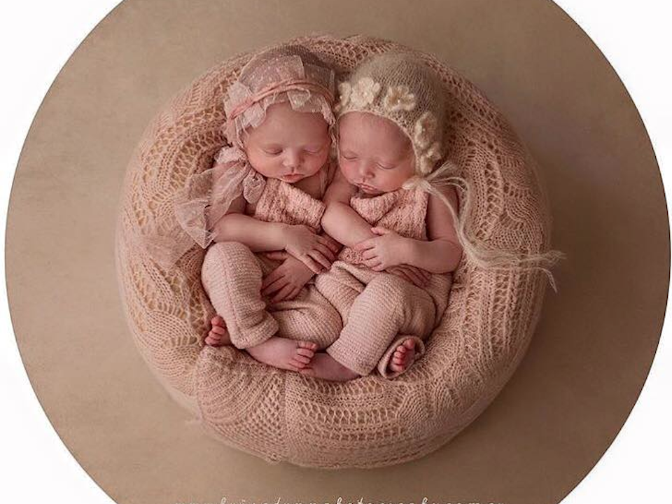 Newborn photo of identical twin baby girls wearing pastel pink