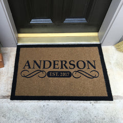 tan doormat with black border and name and date centered on porch