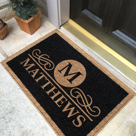 black doormat with tan border, name and initial  on porch