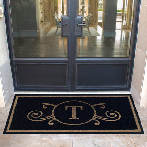 black and tan doormat with initial centered flourish on porch