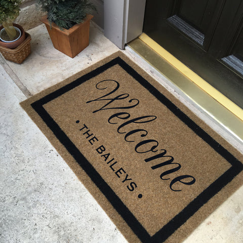 black and tan doormat with family name under Welcome on porch