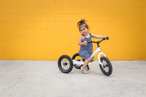 child on a white tricycle