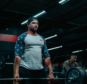 Athlete deadlifts a heavy weight while wearing a patriotic star spangled supplements CBD baseball tee.