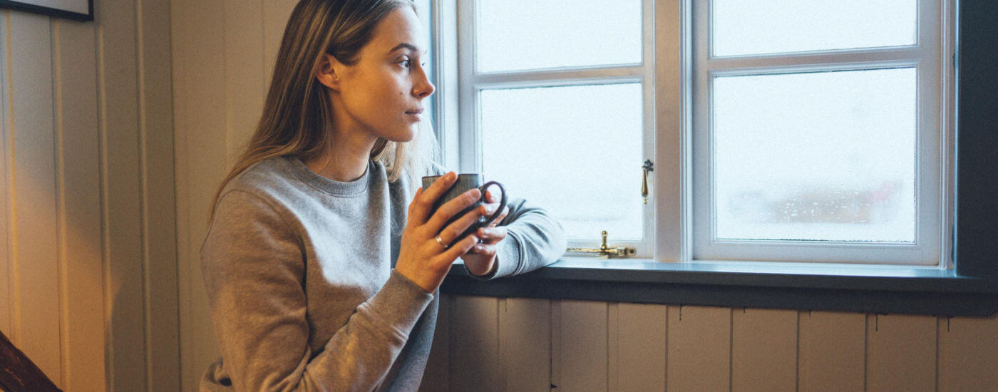 Girl staring out of window with mug of tea