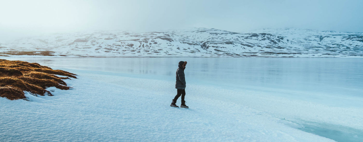 Man walking across ice alone in puffer coat