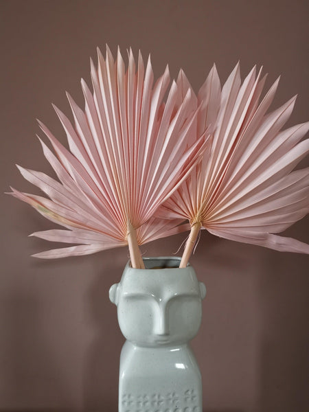 Three dried pink palms in a vase