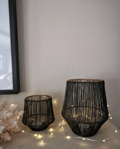 A pair of black and gold reeded lanterns