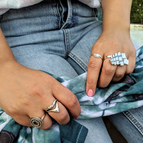 Navona Handmade - Three Rivers Photoshoot sterling silver rings against jeans and a teal tea towel