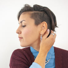 Load image into Gallery viewer, Female model with dark brown hair wearing a blue button down shirt, burgundy cardigan, silver spike earrings, and a silver and sapphire ring.