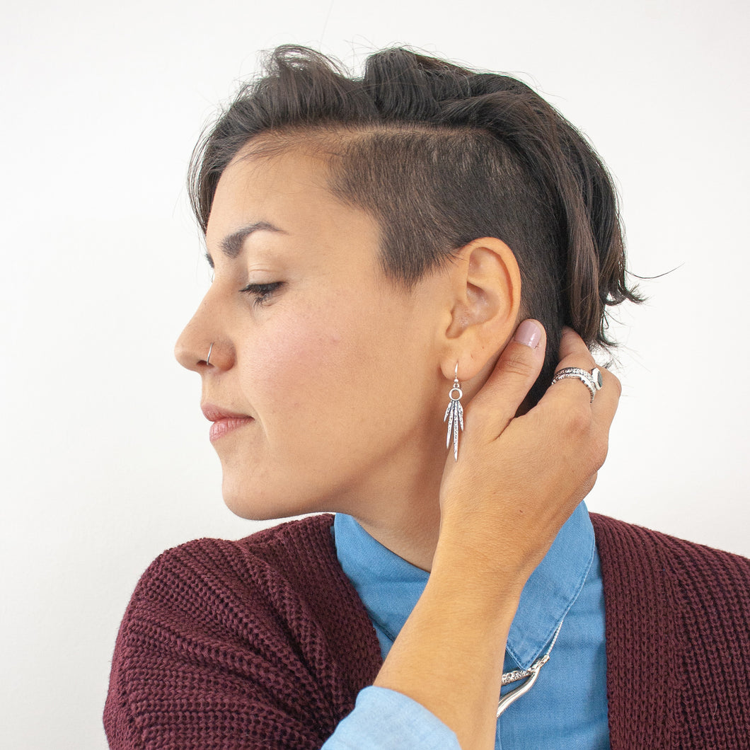 Female model with dark brown hair wearing a blue button down shirt, burgundy cardigan, silver spike earrings, and a silver and sapphire ring.
