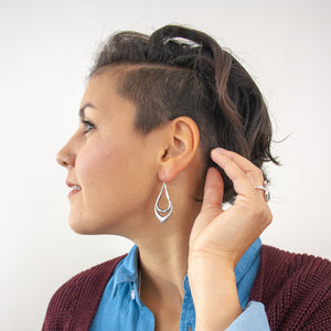 Profile view of a smiling female model with short brown hair. Her hand is cupping her earlobe, and highlighting the sterling silver dangle earring she is wearing.
