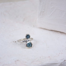 Load image into Gallery viewer, A sterling silver ring sits on a cream backdrop. The ring has a bezel-set hexagon sapphire gemstone and a bezel-set raw sapphire set into it.