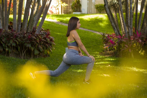 woman in blue yoga pants sitting on green grass field photo