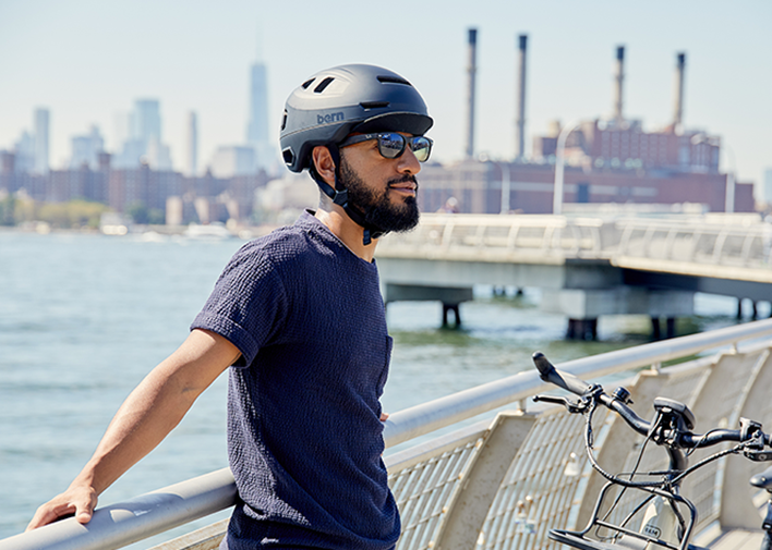 Man wearing Matte Navy Hudson with flip visor gazing toward the city along the Hudson river New York, New York.