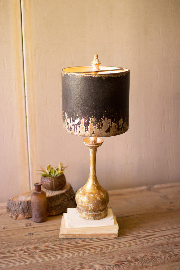 table lamp with round wooden base and black and gold metal shade