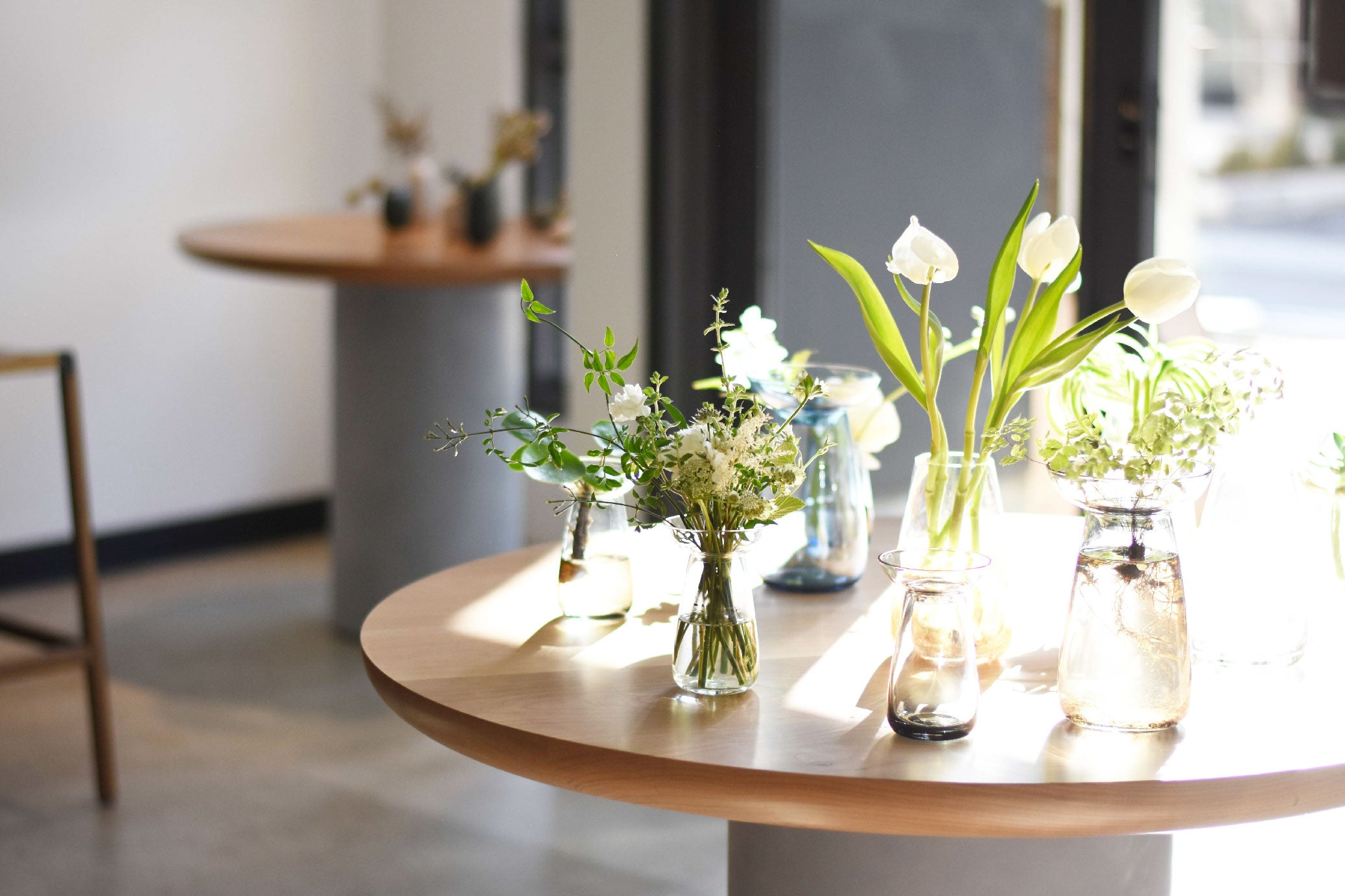 Assortment of flowers in AQUA CULTURE VASES on display table