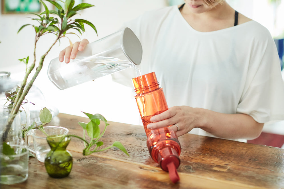 Mayo Uchida pouring water into red WORKOUT bottle