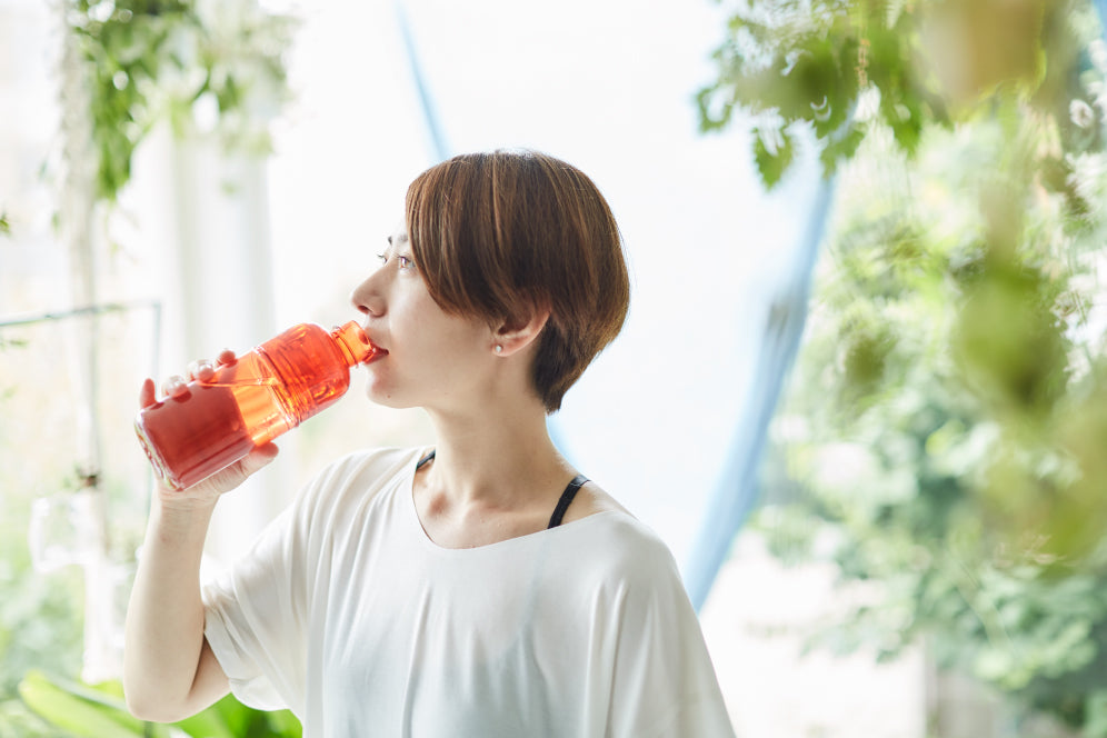 Mayo Uchida drinking out of the red WORKOUT bottle